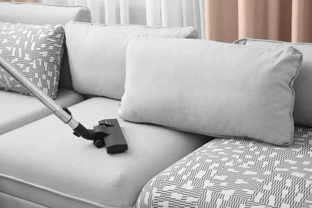 Cleaning couch with vacuum cleaner at home