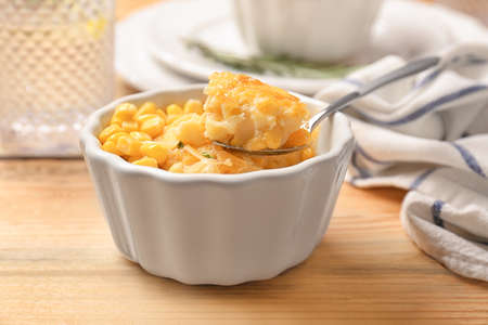 Ramekin and spoon with corn pudding on table