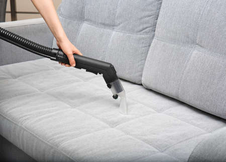 Woman cleaning couch with vacuum cleaner at home Imagens