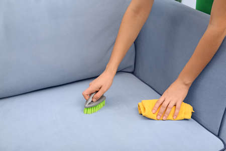 Woman cleaning couch with brush and duster at home