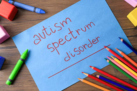 Colorful pencils, cubes and paper with words Autism spectrum disorder on wooden background