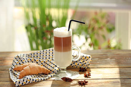 Glass with latte macchiato on table Stock Photo