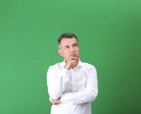 Mature man in white shirt on color background