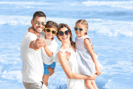 Happy family taking selfie on sea beach at resort