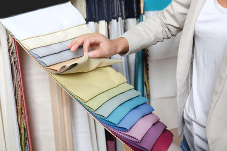 Young woman choosing fabric for new curtains in shop Stockfoto