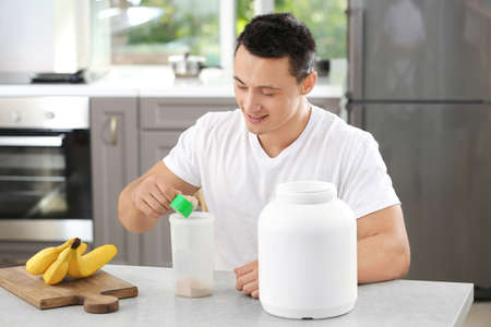 Young sporty man preparing protein shake at table Stock Photo - 101069878
