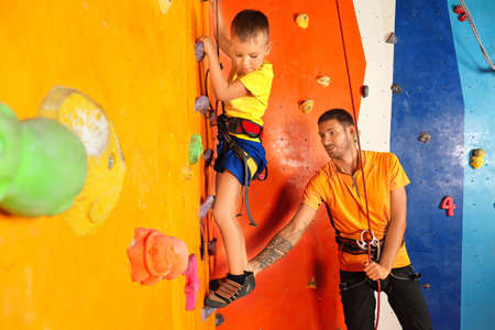 Little boy with trainer in climbing gym