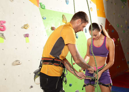 Coach teaching young woman to handle with belay in climbing gym