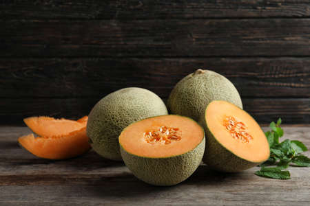 Fresh ripe melons on wooden background Imagens