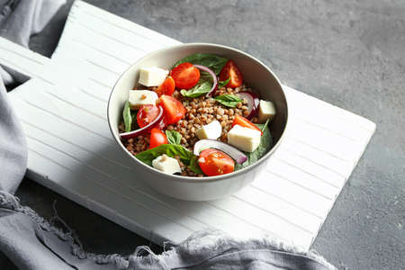 Bowl with buckwheat porridge, vegetables and cheese on table