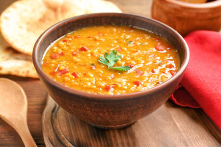 Bowl with tasty lentil soup on table