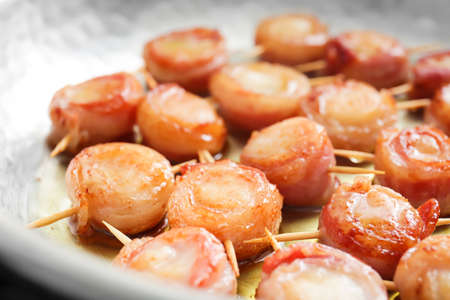 Frying pan with bacon wrapped scallops, closeup