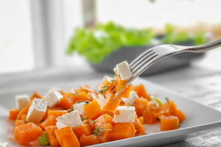 Fork with delicious sliced sweet potato over plate