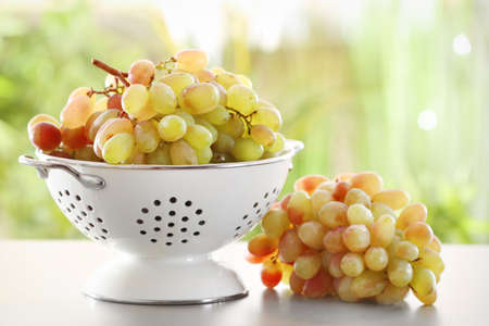 Colander with fresh ripe grapes on table outdoors