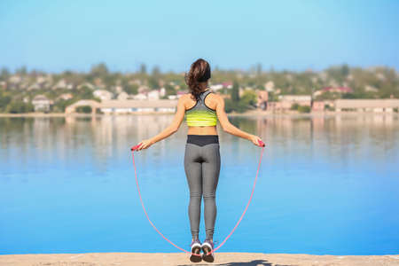 Young woman skipping rope near river