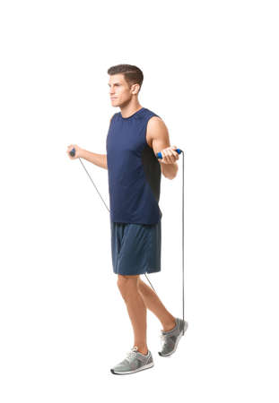 Young man with jumping rope on white background