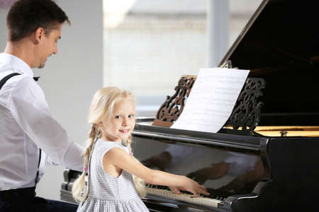 Little girl and young man playing piano indoors