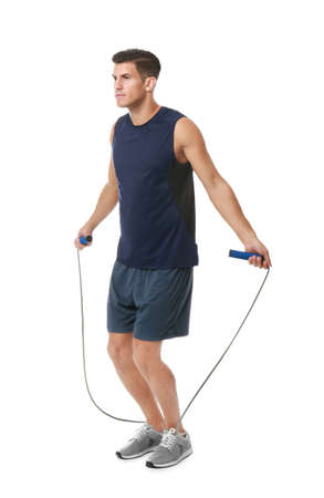 Young man skipping rope on white background