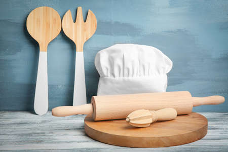 Kitchen utensils and chef hat on table against wall Stock Photo