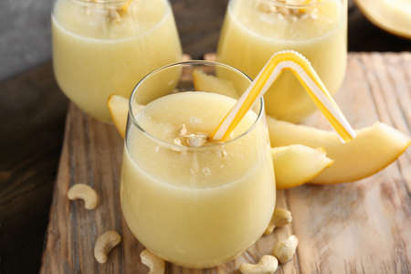 Glass of fresh melon smoothie on wooden board, closeup Stock Photo