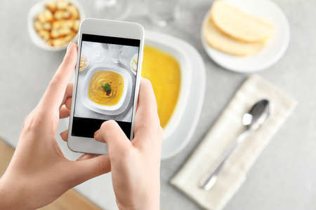 Blogger taking photo of lentils creme soup with cell phone
