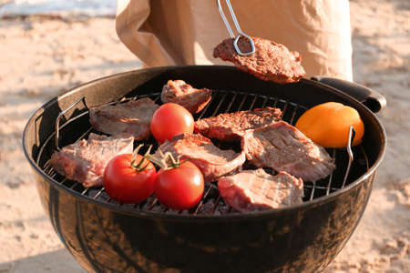 Man cooking steaks and vegetables on barbecue grill, outdoors 版權商用圖片