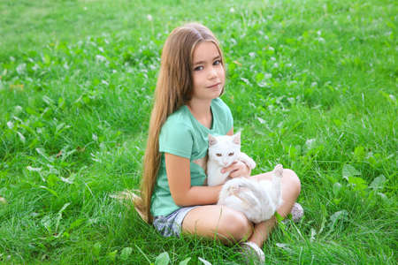 Cute little girl with white cat sitting on grass outdoors
