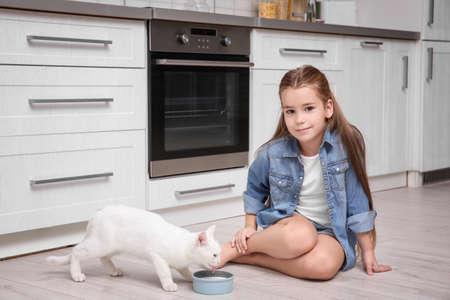 Little girl and white cat on floor indoors