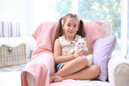 Little girl sitting in armchair with white cat indoors
