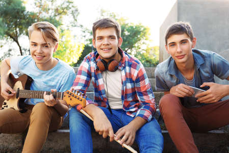 Teenager musicians sitting on steps outdoors