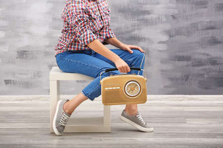 Young woman with retro radio sitting on stool indoors Stock Photo
