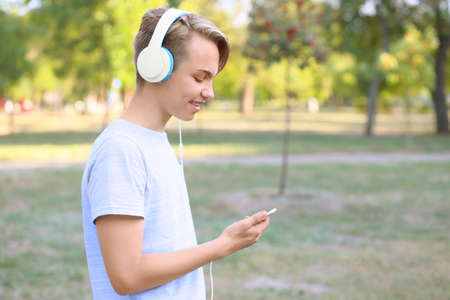 Teenager boy with headphones listening to music outdoors Stock Photo