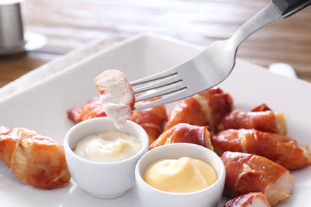 Dipping bacon wrapped chicken into gravy boat with sauce on plate