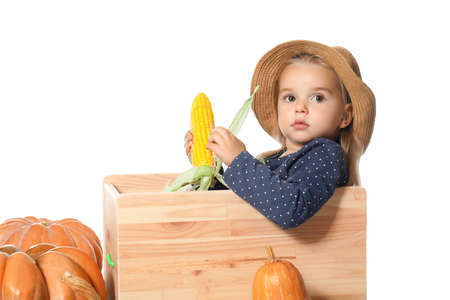 Adorable little girl in hat with vegetables on white background