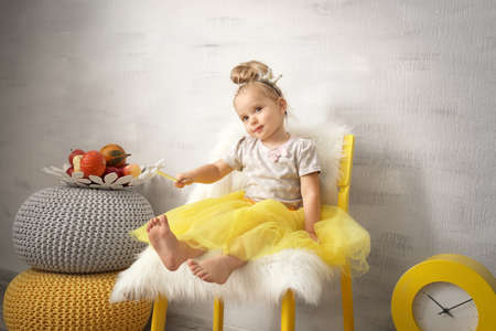 Adorable little girl with magic wand indoors