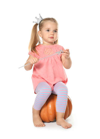 Adorable little girl with magic wand sitting on big pumpkin against white background