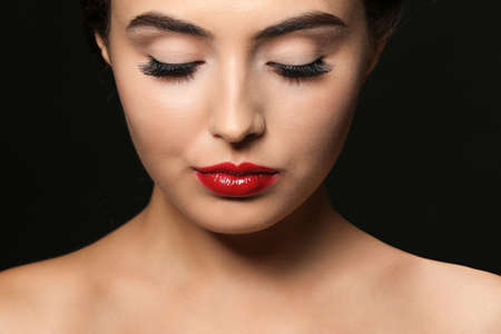 Beautiful young woman with eyelash extensions on dark background