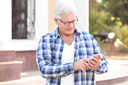 Handsome mature man with cell phone outdoors