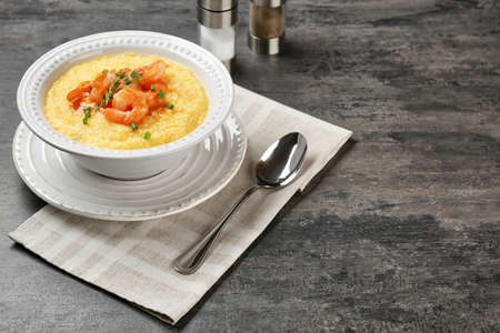 Bowl with fresh tasty shrimp and grits on table
