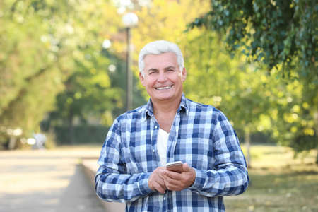 Handsome mature man with cell phone in park Stock Photo