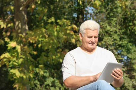Handsome mature man with tablet in park