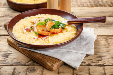 Plate with fresh tasty shrimp and grits on wooden table