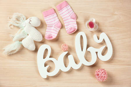 Gifts for baby shower on wooden background