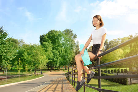 Hipster girl with skateboard sitting on fence in park