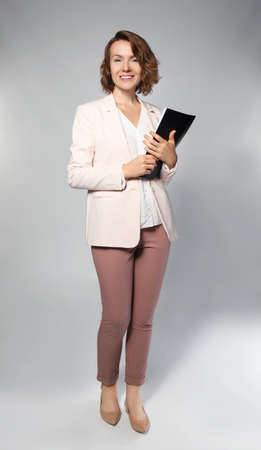 Female manager with notebook on grey background