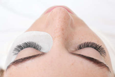 Young woman undergoing eyelash extensions, closeup Stock Photo