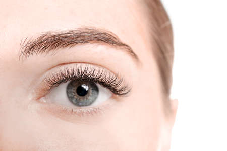 Young woman with eyelash extensions on white background, closeup