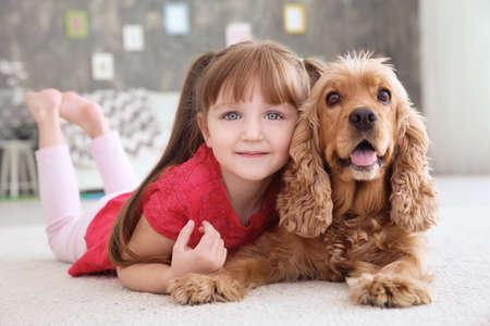 Cute little girl with dog at home Reklamní fotografie