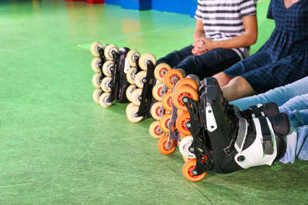 Groep tieners die rolschaatsen binnen dragen, close-up Stockfoto