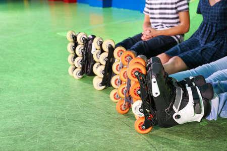 Group of teenagers wearing roller skates indoors, closeup
